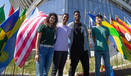 A group of students in front of international flags and the student union.