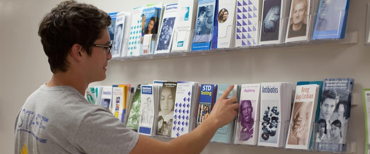 Male student looks at health brochures.