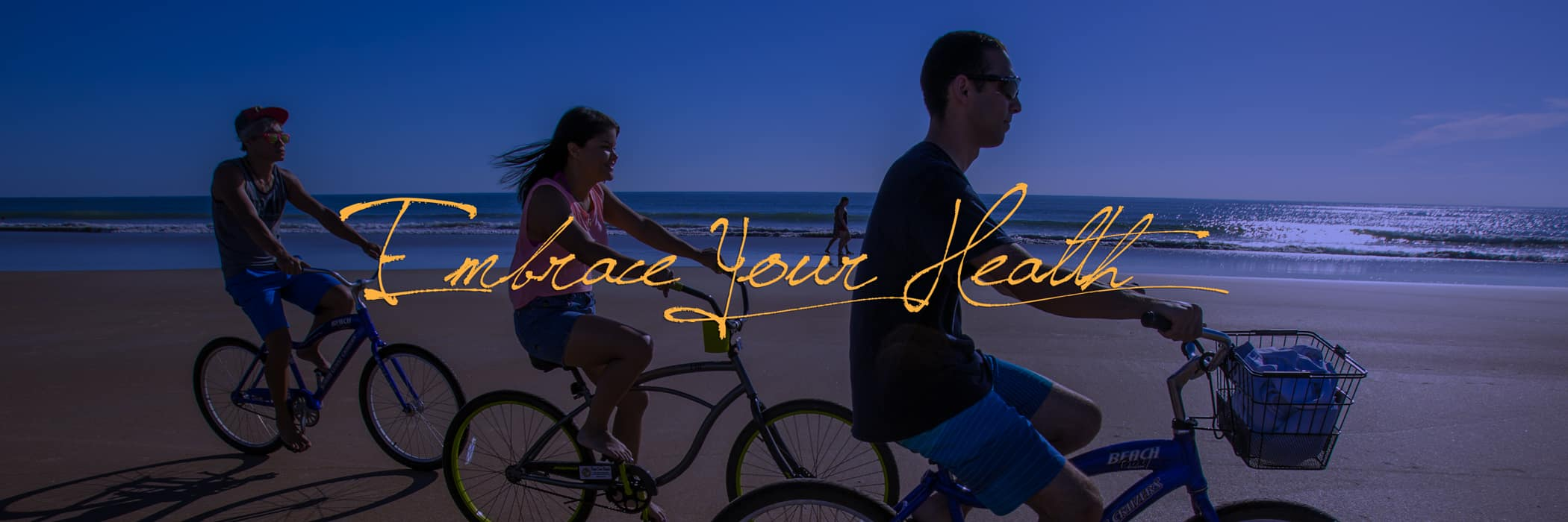 Students riding bicycles on the beach with the text, 'Embrace your health,' on top.