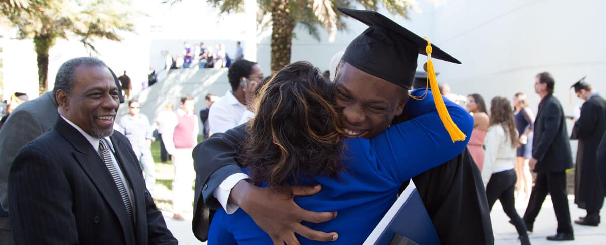 a student hugs his mom at graduation