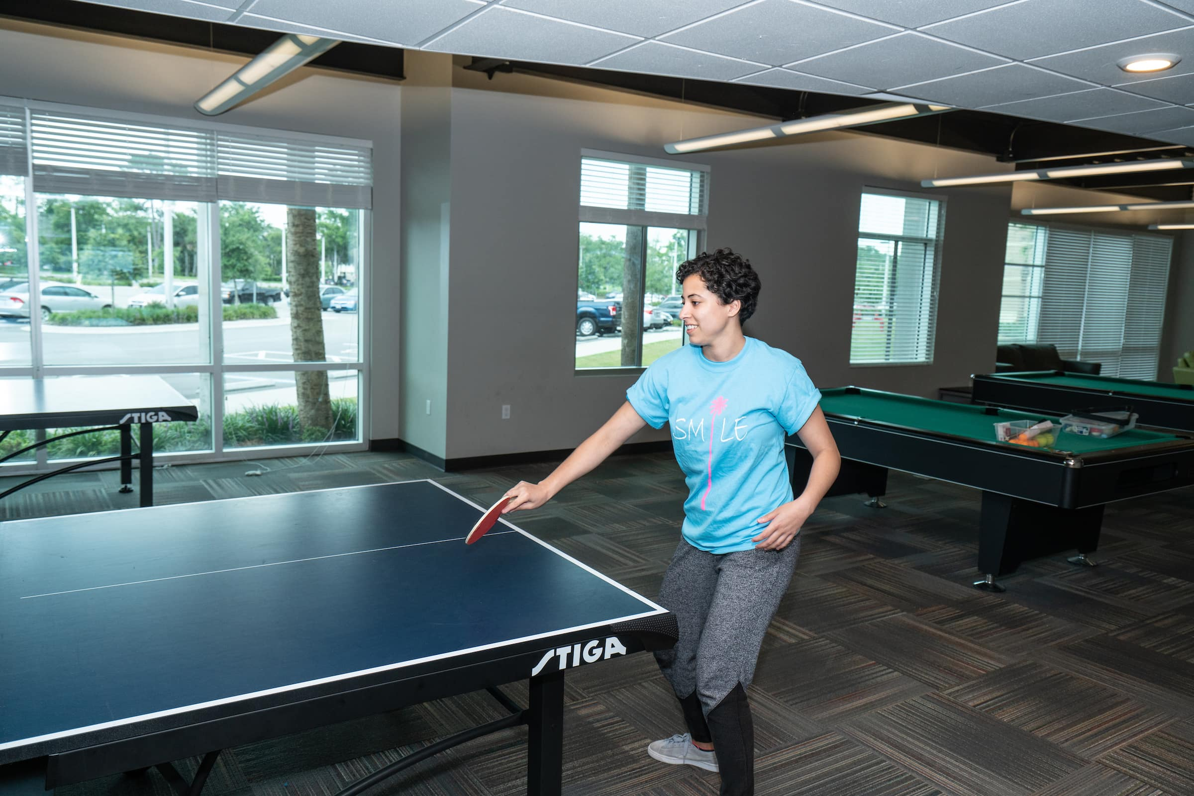 A student plays ping pong with a pool table in the background in New hall.