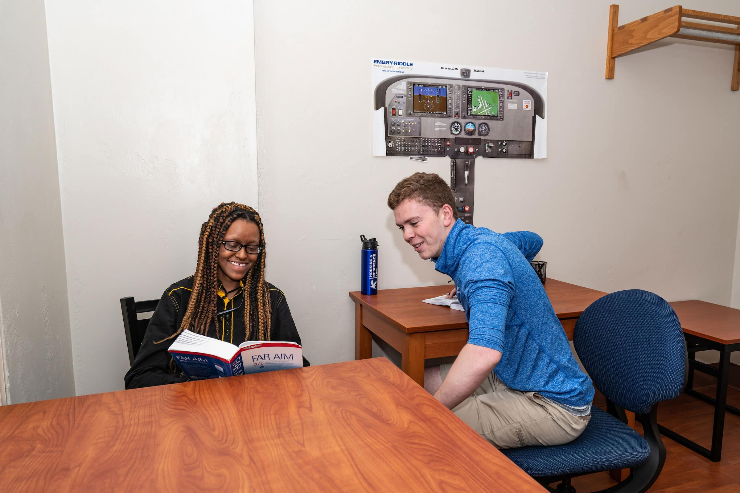 Students play a game at a community table in a Stimpson Hall room.