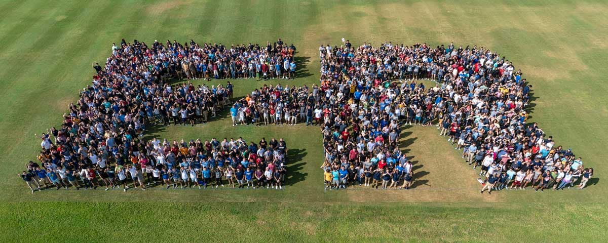 Students form a large E and R in a field.