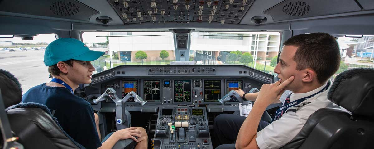 Pilot and future student sit in a cockpit.