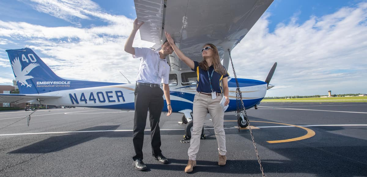 Flight Instructor Tyler Rispoli does a pre-flight check with Sydney Pilling on the flight line at Embry-Riddle Aeronautical University's Daytona Beach Campus.