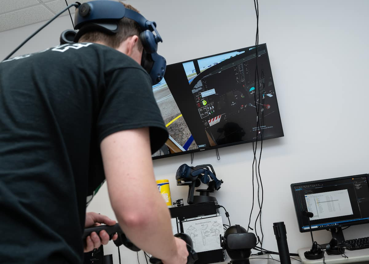 A student participates in the College of Aviation's VR lab using a virtual reality checklist to preflight a Cessna 172.