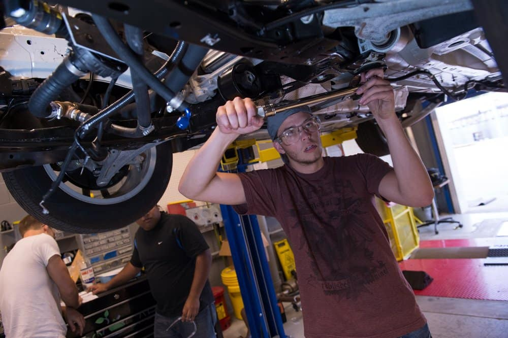 A student works on the underside of the EcoCar