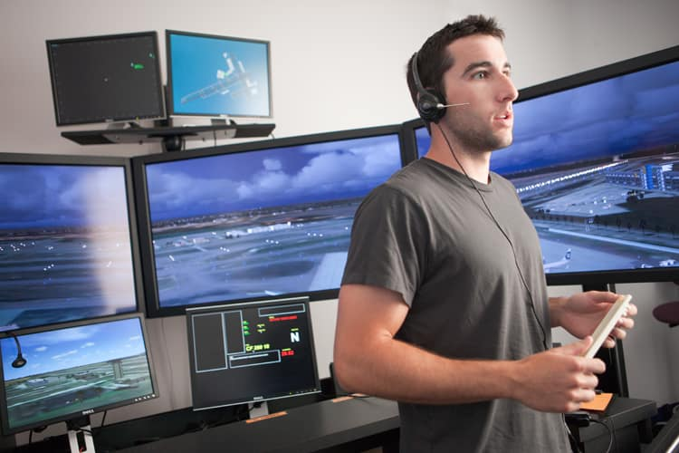 Student stands in front of Air Traffic Control screens