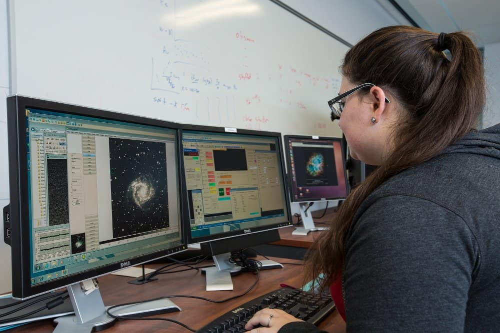 A student works on a computer in the Astrophysics and Controls Lab