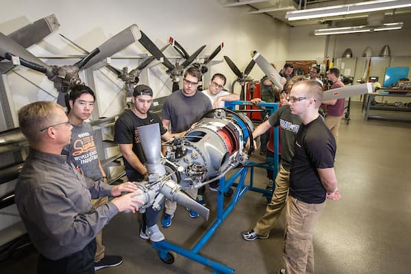 Professor talks to students around engine in the Basic Engine and Propeller Systems Lab