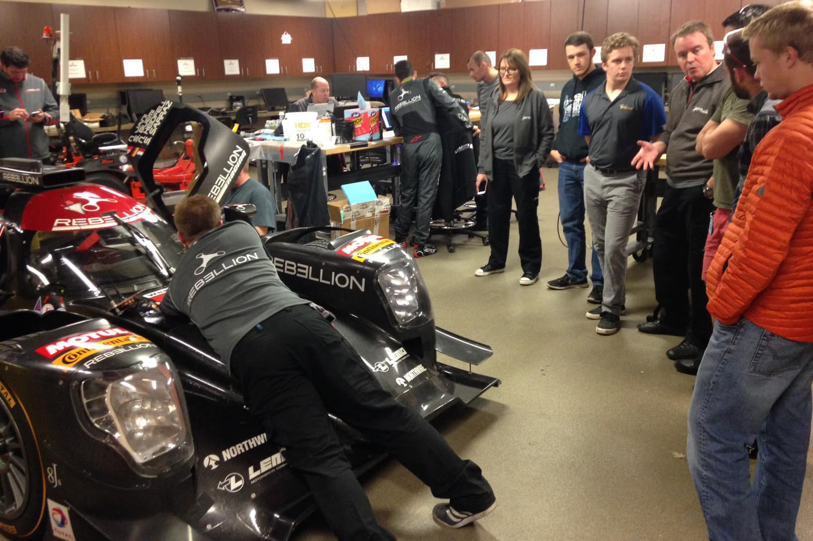 Students and staff examine a car in the Center for Motorsports Engineering