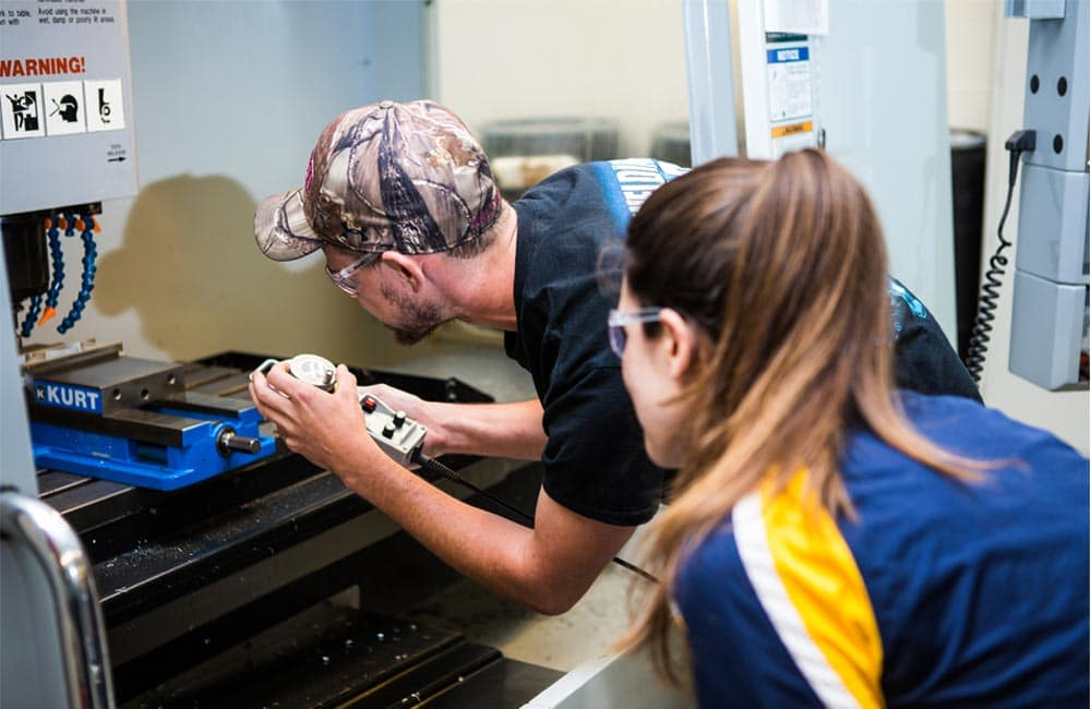 Students work on a drill press in the CNC and Welding Laboratory