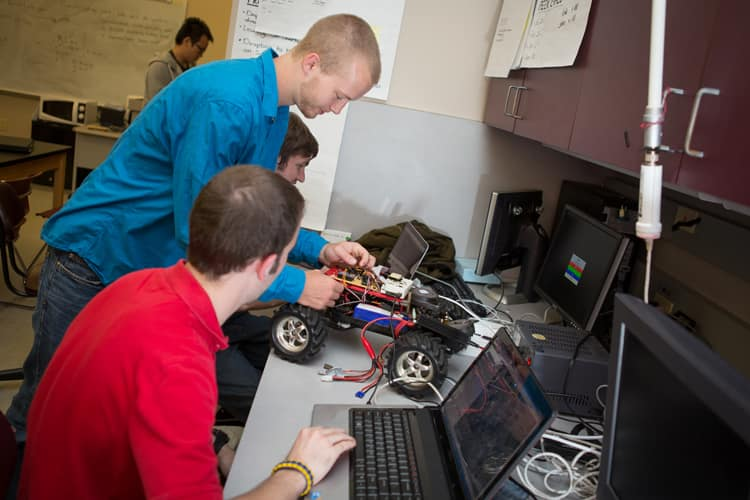 Students work on a remote-control car at the ECSSE Capstone Design Laboratory