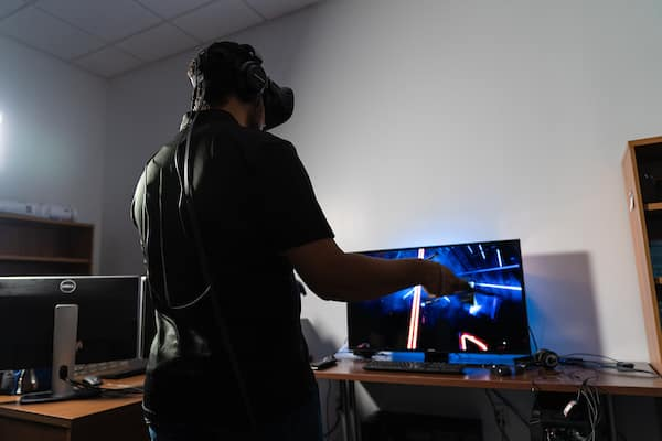 Student with VR headset plays Beatsaber