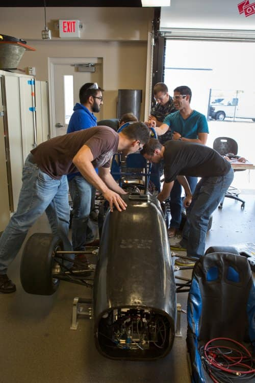 Stuedents work on a car in the High Performance Vehicle Laboratory