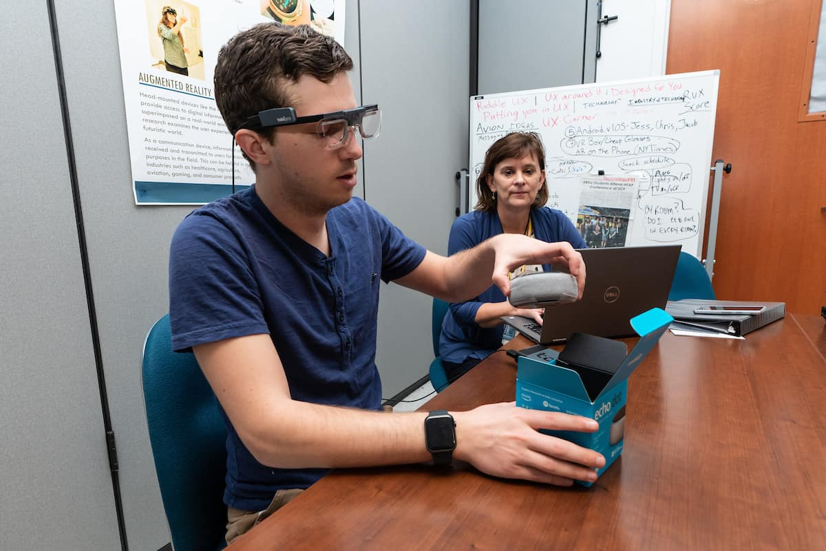 Graduate student Jacob Benedict works with Dr. Barbara Chaparro to demonstrate how they can use the TobiiPro augmented reality glasses to observe someone doing a product unboxing in the Human Factors User Experience Lab.