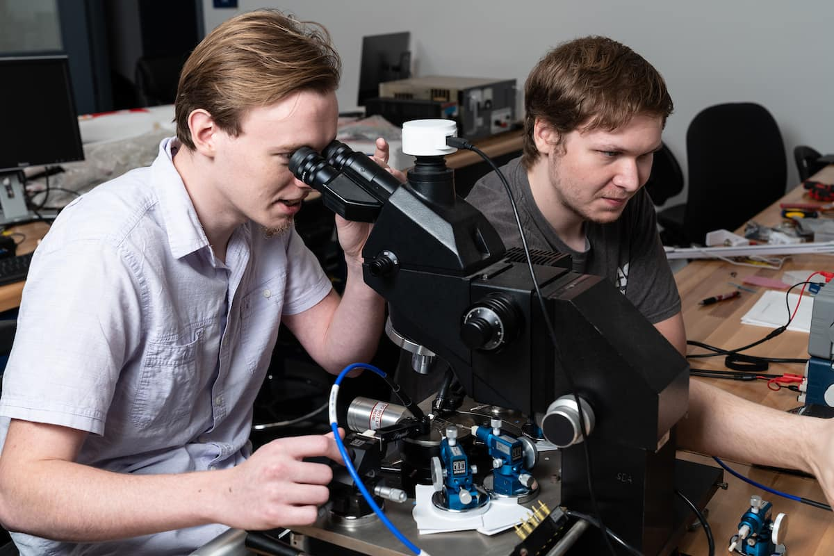 Daniel Sommer and John Sahr working with microscopes and probes to test the power properties of antenna materials.