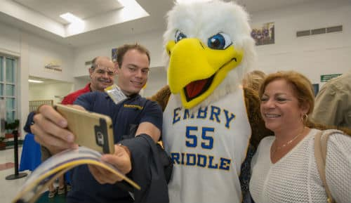 a student and his parents take a selfie with Ernie the Eagle