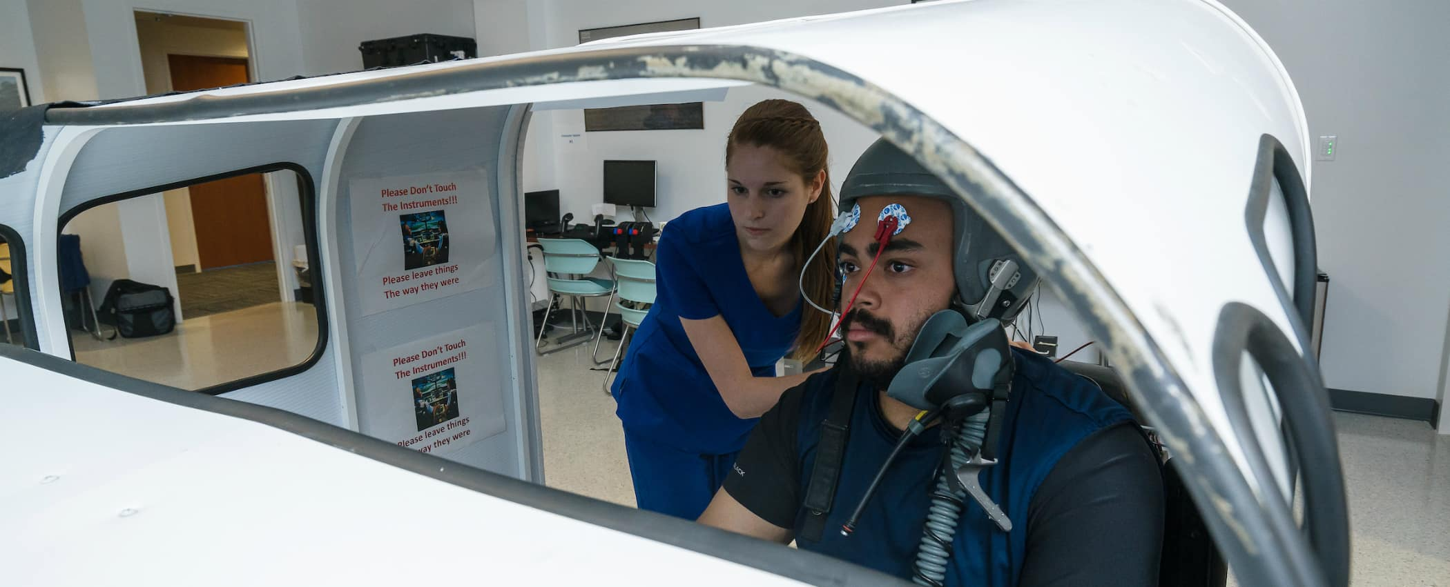 Dr. Bert Boquet works with a student and lab technician to measure pilot performace in a simulator.