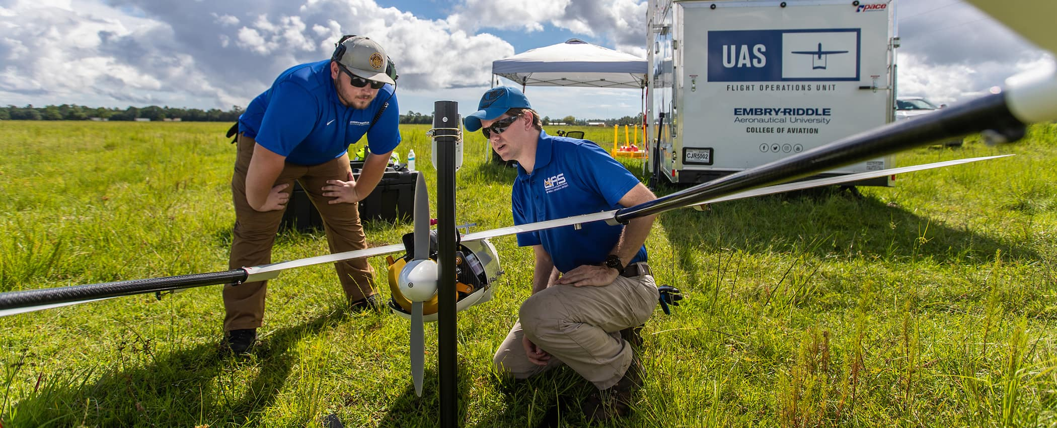 Austin Noble, student and lab assistant, left, and Michael Zebehazy,  UAS Maintenance and Inventory Manager and Crew Chief, prepare the Penguin C UAV platform for flight in West Bunnell, July 29, 2019.  (Embry-Riddle/David Massey)